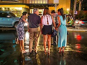 20 SEPTEMBER 2013 - BANGKOK, THAILAND:  A western man with three Thai women waits for a taxi on Soi Cowboy in Bangkok. Soi Cowboy is one of the notorious Entertainment Districts in Bangkok. Entertainment District has emerged as euphemism for red light district. Prostitution is officially illegal in Thailand but it is widely condoned. For western men, Soi Cowboy, along with Soi Nana and Patpong are among the most well known entertainment districts in Bangkok.      PHOTO BY JACK KURTZ