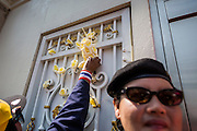 22 DECEMBER 2013 - BANGKOK, THAILAND:  An anti-government protestor puts flowers in the gate of the home of caretaker Prime Minister Yingluck Shinawatra. Hundreds of thousands of Thais gathered in Bangkok Sunday in a series of protests against the caretaker government of Yingluck Shinawatra. The protests are a continuation of protests that started in early November and have caused the dissolution of the Pheu Thai led government of Yingluck Shinawatra. Protestors congregated at home of Yingluck and launched a series of motorcades that effectively gridlocked the city. Yingluck was not home when protestors picketed her home.    PHOTO BY JACK KURTZ