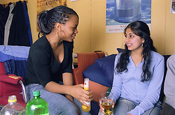 Two teenage girls drinking alcohol and talking,