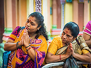 05 JUNE 2015 - KUALA LUMPUR, MALAYSIA:   Women pray during the midday prayer in Sri Mahamariamman Temple, the oldest functioning and most important Hindu temple in Malaysia. The principal deity in the temple is Mariamman,  a deity that is popularly worshipped by overseas Indians, especially Tamils, because she is looked upon as their protector during the sojourn to foreign lands. Mariamman is a manifestation of the goddess Parvati, an incarnation embodying Mother Earth with all her terrifying force. She is associated with disease and fever and protects her devotees from unholy or demonic events.    PHOTO BY JACK KURTZ