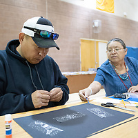 On Thursday in Twin Lakes, Navajo Language teacher Veda Yazzie, right, shows James Lewis, 48, left, which constellations to apply colored gems to during the Family Math Night held at Twin Lakes Elementary School.