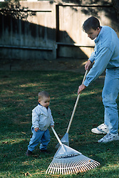 man showing little boy how to rake a lawn