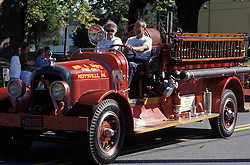 Americana antique fire engine leads march in small town holiday celebration parade. Stock photo