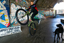 Watched by Mac Ferarri's dog Xuki, Liam Ross, 17,  does wheelie in a grafitti tunnel near London Bridge. Bikestormz is the brainchild of leader Mac Ferrari, a group of young trick cyclists who are encouraged to put knives down and enjoy the healthy, positive side of urban youth culture by joining together  and developing their cycling skills. . London, September 27 2019.