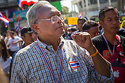 """15 JANUARY 2014 - BANGKOK, THAILAND: SUTHEP THAUGSUBAN, former Deputy Prime Minister of Thailand and leader of the Shutdown Bangkok anti-government protests, walks up Sukhumvit Road in Bangkok during a protest march. Tens of thousands of Thai anti-government protestors continued to block the streets of Bangkok Wednesday to shut down the Thai capitol. The protest, """"Shutdown Bangkok,"""" is expected to last at least a week. Shutdown Bangkok is organized by People's Democratic Reform Committee (PRDC). It's a continuation of protests that started in early November. There have been shootings almost every night at different protests sites around Bangkok. The malls in Bangkok are still open but many other businesses are closed and mass transit is swamped with both protestors and people who had to use mass transit because the roads were blocked.    PHOTO BY JACK KURTZ"""