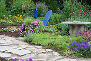 63821-21904 Flower garden with blue Adirondack chair, bird bath and blue birdhouse.  Butterfly Bushes, Peach & Purple Verbenas, Yellow Lantana (Lantana camara), Raspberry Blast petunias & Diamond Frost Euphorbia in blue pot, Karl Forster grass, sedums, Marion Co., IL