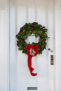 A traditional low country Magnolia leaf Christmas wreath hangs from a wooden door on a historic home along King Street in Charleston, SC.