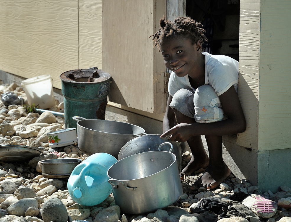 A girl washes dishes in the doorway of her family's home in Camp Corail, a controversial resettlement of earthquake survivors north of Port-au-Prince, Haiti. Thousands of families were relocated to Corail from flood-prone areas of the capital in 2010, yet the promises of jobs that lured them there failed to materialize.
