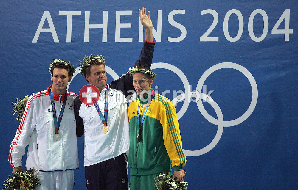 Gary Hall from the USA (C) shows off his gold medal next to silver medalist Duje Draganja from Croatia (L) and bronze medalist Roland Mark Schoeman from South Africa during the flower ceremony of the men's 50m Freestyle final at the Athens Olympic Aquatic Centre, Friday, 20 August 2004.       (Photo by Patrick B. Kraemer / MAGICPBK)