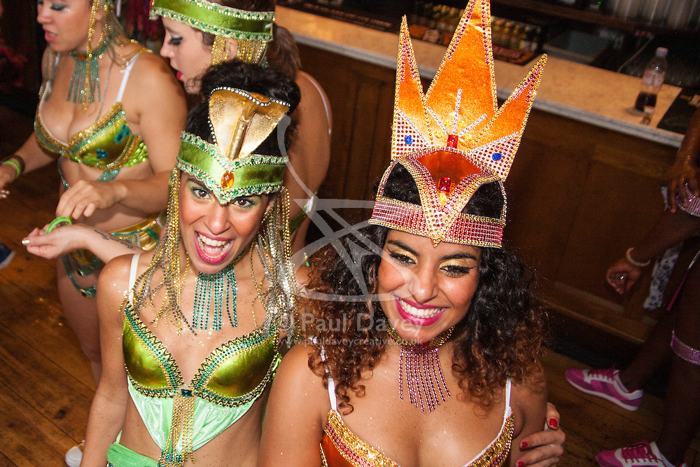 London, August 25th 2014. Good spirits are evident despite the weather as final touch ups to costumes are made as Notting Hill Carnival goers prepare to party despite the pouring rain.