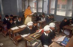 School girls and boys sitting at desks reading books with female teacher supervising in senior secondary modern school; Punjabi University; Patiala; Punjab; India,