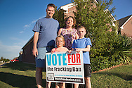 The Bush family stand behind a sign supporting a fracking ban on their lawn in Denont Texas. They live between two fracking sites.  On November 4th, 2014 citizens in Denton passed a ban for fracking with in the city limits despite being out spent by those against the ban by ten to one beofre the election,<br /> The Barnett Shale,  which Denton sits on top of,  is rich with natural gas and has experienced a boom from hydraulic fracturing.