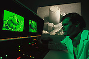 Micro Technology: Micromechanics: Dale Emery at the controls of a scanning electron microscope (SEM). The image from the microscope is displayed on the TV-type screens. The subject under the microscope is a 250 micron-diameter wobble motor, a micromechanical device. Just visible in the display running diagonally across the right of the screen is a human hair included for comparison. University of Utah, Salt Lake City, USA. Model Released