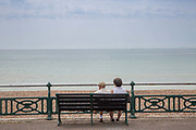 An elderly couple sitting on a park bench along the Brighton and Hove seafront on the 19th July 2018 in Brighton in the United Kingdom.