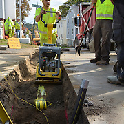"BATH, Maine -- 10/8/14 -- Tyler Rowe of Enterprise Trenchless Technology Incorporated closes up a gas line trench across Washington St. in Bath on Wednesday with a weight compactor. Gas lines began going in on Aug 20. Washington St -- from Centre to Bowery St -- is complete and the company is now working their way down the side streets. In the foreground is the 2"" gas line used to deliver natural gas to Bath homes. Equipment Operator Josh Worth said,<br />