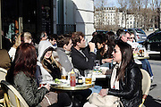 People sit in a café near Notre Dame, enjoying the sun on a Sunday afternoon in February in Paris