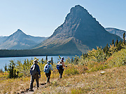 """Sinopah Mountain, hikers, and Two Medicine Lake, in Glacier National Park, Montana, USA. Since 1932, Canada and USA have shared Waterton-Glacier International Peace Park, which UNESCO declared a World Heritage Site (1995) containing two Biosphere Reserves (1976). Rocks in the park are primarily sedimentary layers deposited in shallow seas over 1.6 billion to 800 million years ago. During the tectonic formation of the Rocky Mountains 170 million years ago, the Lewis Overthrust displaced these old rocks over newer Cretaceous age rocks. Glaciers carved spectacular U-shaped valleys and pyramidal peaks as recently as the Last Glacial Maximum (the last """"Ice Age"""" 25,000 to 13,000 years ago). Of the 150 glaciers existing in the mid 1800s, only 25 active glaciers remain in the park as of 2010, and all may disappear by 2020, say climate scientists."""