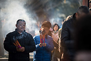 Worshipers make offerings of incense sticks at Longhua Temple in Shanghai, China, on Tuesday, Feb. 9, 2016.