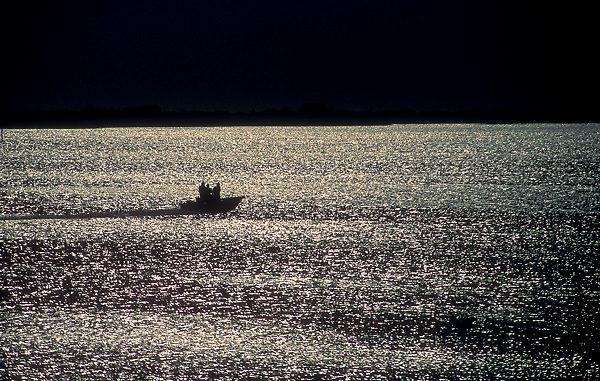 Stock photo of the silhouette of a speedboat passing through the bay