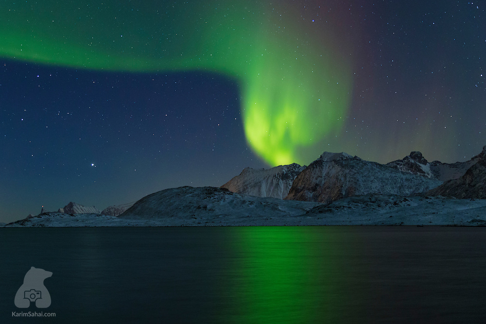 The Aurora Boralis dances and glows intensely over the mountains surrounding the small village of Fredvang, in norwegian arctic islands of Lofoten.