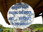 A sign to a metalworkers house who makes spoons and bracelets from recycled aluminium sourced from Vietnam War debris and melted in an earthen kiln in Ban Naphia, a remote Tai Phouan village in mountainous Xieng Khouang Province in Northern Laos. Laos is the most bombed country, per capita, in the world with more than two million tons of ordnance dropped on it during the Vietnam War from 1963 to 1974.12 artisan families began transforming war scrap into spoons (150,000 per year) in the 1970s to supplement subsistence farming activities. Supported by the Swiss NGO Helvetas, the project works to make the scrap metal supply chain safer for artisans and scrap collectors by collaborating with organisations such as Mines Advisory Group (MAG) that specialise in unexploded ordnance removal and education. More recently the villagers have started making bracelets and other items.