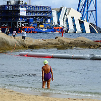 ISOLA DEL GIGLIO, ITALY - SEPTEMBER 15:  A woman in swimsuit walks in front of the wreckage of the Costa Concordia on September 13, 2013 in Isola del Giglio, Italy. The Costa Concordia is reportedly due to be righted beginning on the morning of September 16, then, if the operation is successful, it will be towed away and scrapped.  (Photo by Marco Secchi/Getty Images)