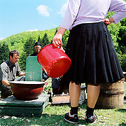 A Romanian peasant farmer waits for her sheep's milk to be weighed at a Measurement of the Milk festival, Botiza, Maramures, Romania. The Measurement of the Milk festivals take place at the beginning of May, when the shepherds bring the flocks, which have spend a few days grazing in the hills, to meet the villagers at a clearing where the measurement will take place.  The sheep are milked by their owners, and the yield of each family's animals measured to determine the quota of cheese that they will receive during that season.