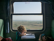 Child drawing in a train while mother is sleeping.