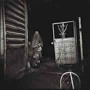 Two burqa-clad women rest inside a furniture shop in Kabul.
