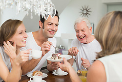 Family with adult children at table eating cake