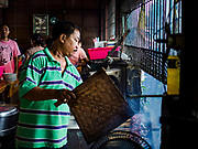 06 AUGUST 2017 - MENGWI, BALI, INDONESIA: A man cooks sate (grilled meat) in the Bringkit Market, about 30 minutes from Denpasar. Bringkit Market is famous on Bali for its Sunday livestock and poultry market. Hundreds of the small Bali cows are bought and sold there every week. Bali's local markets are open on an every three day rotating schedule because venders travel from town to town. Before modern refrigeration and convenience stores became common place on Bali, markets were thriving community gatherings. Fewer people shop at markets now as more and more consumers go to convenience stores and more families have refrigerators.     PHOTO BY JACK KURTZ