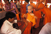 On the final day of the Poy Sang Long, the ordination of novice monks, family members help the boys put on their orange robes, Mae Hong Son, Thailand. April 2003.
