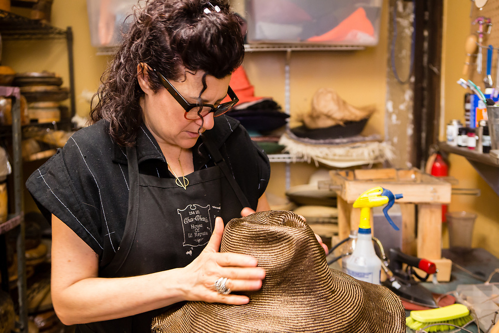 Shaping a steamed straw hat body over a block.