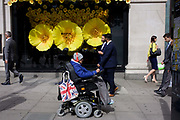 Disabled wheelchair user in front of Apple Watch window display in Selfridges, central London. Wearing red ear phones and wolly hat and coat, the man travels along the street looking out of place with other passers-by all still in summer clothing. With a union jack shopping bag hanging off the rear handle of his wheelchair, the man passes the shop window. Large yellow flowers are being displayed to help promote Apple's new product of the year, its digital Watch. Featured large in the window of Oxford Street's famous department store, the general public walk past the colourful display.