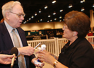 5/1/04 Omaha, Neb.  Warren Buffett signs a bobble head doll for Jan Pedrazzi of See's Candies at the Berkshire Hathaway shareholders meeting at Qwest Center Omaha Saturday morning.  (Photo by chris machian)