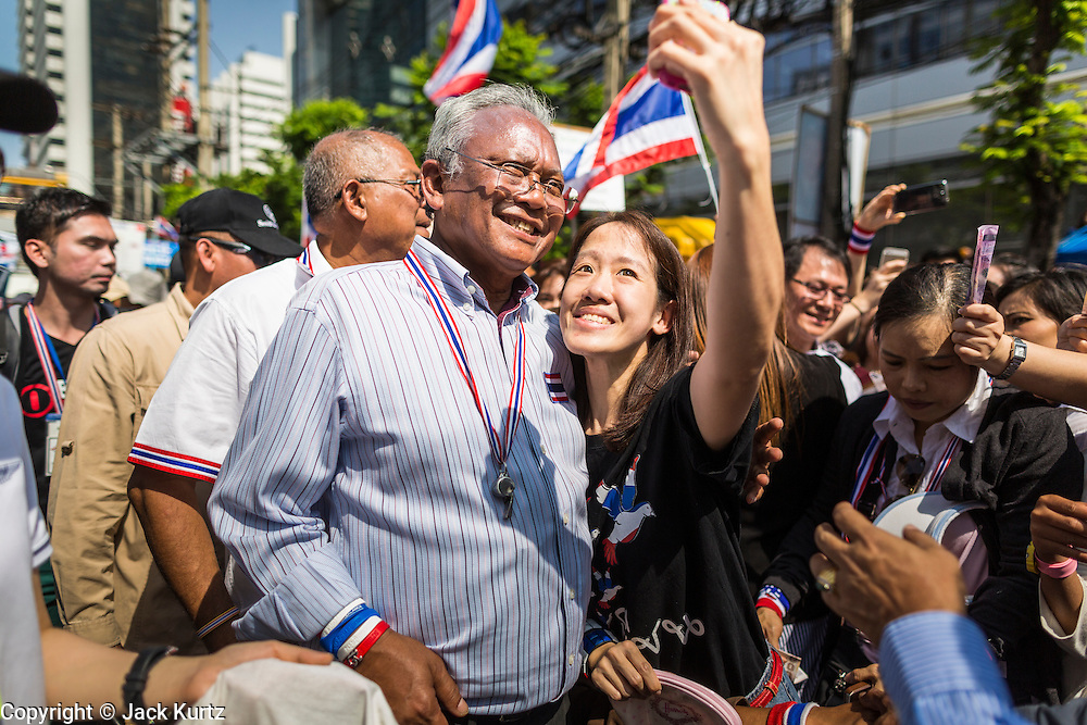 """21 JANUARY 2014 - BANGKOK, THAILAND:  A woman stops SUTHEP THAUGSUBAN for a """"selfie"""" during a march down Thanon Naradhiwas Rajanagarindra in the financial district of Bangkok. Suthep, the leader of the anti-government protests and the People's Democratic Reform Committee (PDRC), the umbrella organization of the protests, led a march through the financial district of Bangkok Tuesday. Shutdown Bangkok has entered its second week with no resolution in sight. Suthep is still demanding the caretaker government of Prime Minister Yingluck Shinawatra resign and the PM says she won't resign and intends to go ahead with the election.    PHOTO BY JACK KURTZ"""