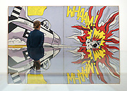 "© Licensed to London News Pictures. 18/02/2013. London, UK A woman stands in front of ""Whaam!"" 1963. Press view for Tate Modern's ""Lichtenstein: A Retrospective"". It is the first major Lichtenstein retrospective for twenty years, bringing together 125 of the artists most definitive paintings. The exhibition is open to the public from 21 February -  27 May 2013.  Photo credit : Stephen Simpson/LNP"