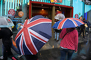 London, UK. Sunday 23rd August 2015. Heavy summer rain showers in the West End. People brave the wet weather armed with umbrellas and waterproof clothing. Union Jack flag umbrella. Leicester Square.