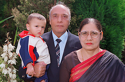 Grandmother and grandfather standing outdoors in garden holding young grandson,