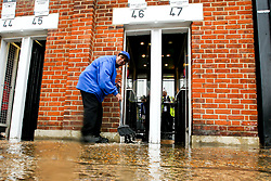 A steward sweeps water away from a flooded turnstile at Craven Cottage - Mandatory by-line: Robbie Stephenson/JMP - 26/08/2018 - FOOTBALL - Craven Cottage - Fulham, England - Fulham v Burnley - Premier League