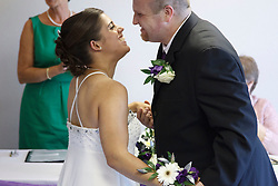 Bride who has cerebral palsy, with groom at wedding ceremony.
