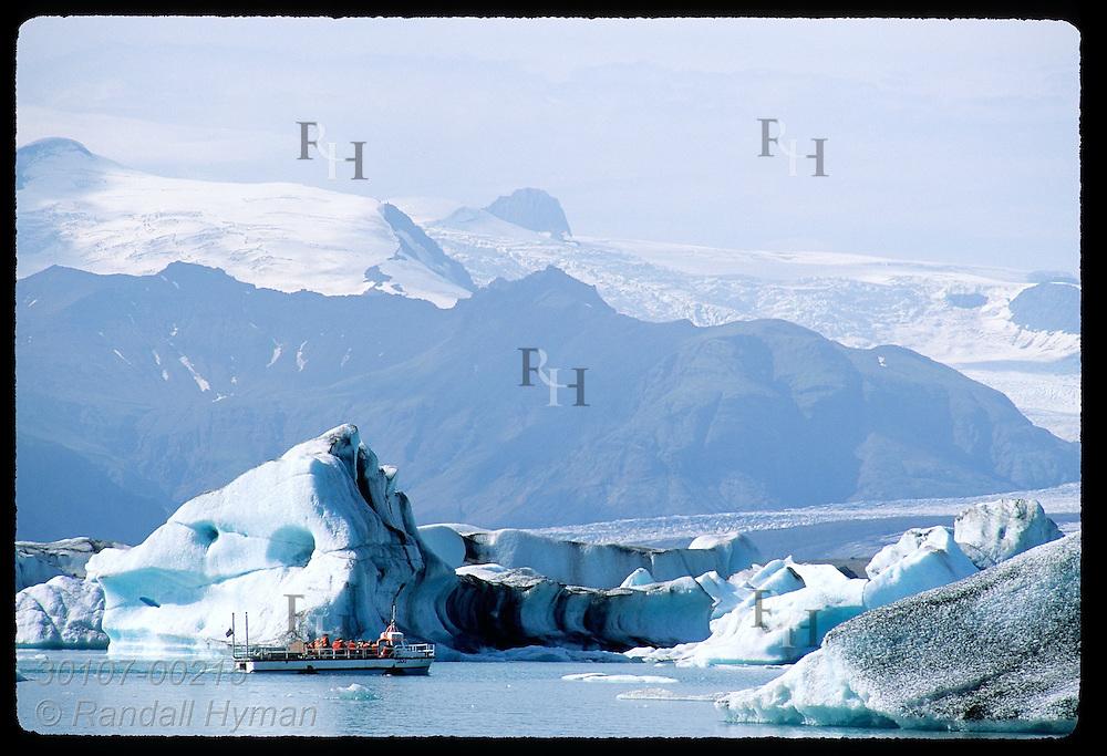 Amphibious boat glides by ice calved from Breidamerkurjokull glacier in Jokulsarlon (Glacier Lagoon) with Vatnajokull in distance; Iceland.