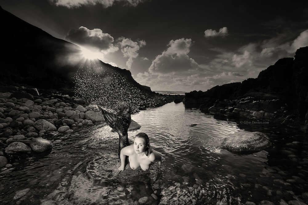 Nominee in Nude / B&W Spider Awards 2017<br /> <br /> She was confused. She'd fallen into a deep sleep in a remote cove but as the morning sun broke over the shadowy headland she realised she was now in the open and clearly visible. <br /> <br /> When she saw me huddled against the nearby rocks hiding from the biting Northerly wind, she froze and then scowled at me. She hadn't been exposed to a man before but I talked reassuringly to her, and she soon came to understand that I posed no threat. <br /> <br /> For maybe twenty minutes she alternated between swimming around the pool and pulling herself up onto the boulders to talk with me. She seemed to enjoy conversation. She loved her newfound confidence in being open in front of a man and she didn't shy away as I asked her questions. I studied her as she studied me and we had an understanding of the fascination in each other. <br />   <br /> As waves started crashing in on the advancing tide, she swam to the far end of the pool. She studied me intently one last time and with a flick of her powerful tail she leapt the rock barrier into the ocean and she was gone.  I knew though that as our paths had now crossed, this wouldn't be our only encounter with each other, and I was right.