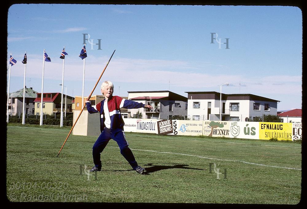 Boy on soccer field about to throw javelin mimics Viking heroes of Saga fame; Saudarkrokur Iceland