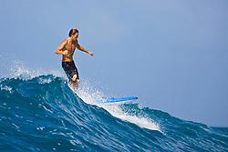 Surfer, enjoying riding rare big ocean waves in Kona Coast, Keauhou Bay, Big Island, Hawaii, Pacific Ocean