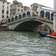The Rialto Bridge (Italian: Ponte di Rialto) is one of the four bridges spanning the Grand Canal in Venice, Italy. It is the oldest bridge across the canal. The present stone bridge, a single span designed by Antonio da Ponte, was finally completed in 1591.