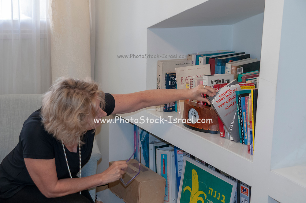 Female therapist is looking through her reference books on a bookshelf in a medical professional's consulting room. Model release Available