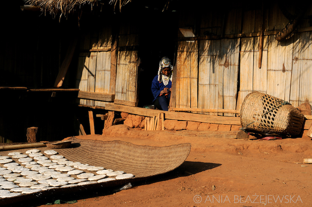 Burma/Myanmar. Akha woman working in her house.