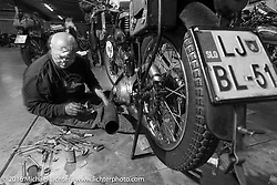 """Sante Mazza of Rimini, Italy works on his 1926 Moto Frera on the  Friday """"Rest Day"""" between stages 7 and 8 of the Motorcycle Cannonball Cross-Country Endurance Run in Junction City, KS., USA. Friday, September 12, 2014.  Photography ©2014 Michael Lichter."""