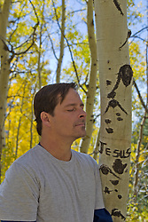 "man near a defaced tree with the name ""Jesus"" carved in the bark"